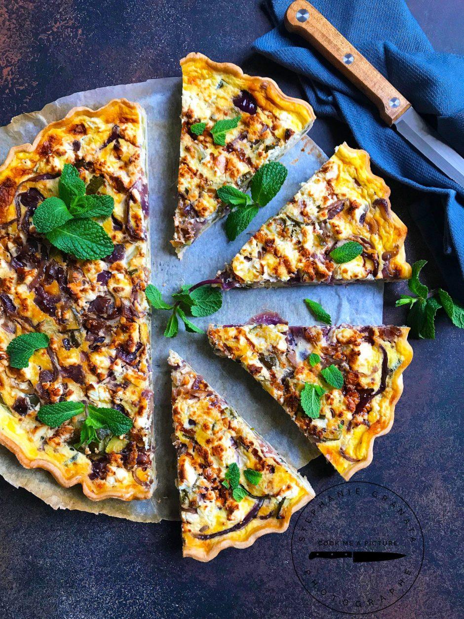 Une délicieuse quiche à la fêta avec des courgettes des oignons rouges de la crème balsamique et de la menthe fraiche